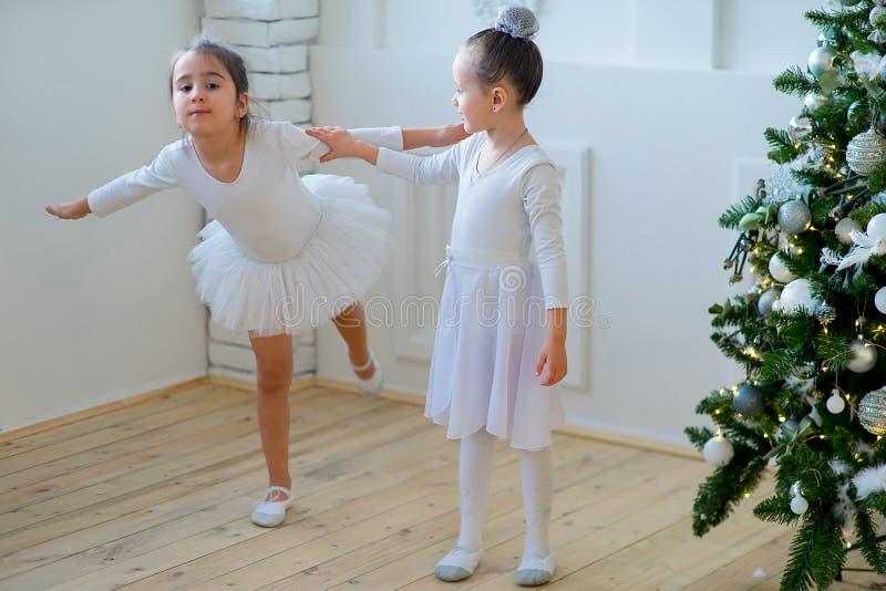 Twee jonge balletdansers die de les leren dichtbij Kerstboom royalty-vrije stock foto