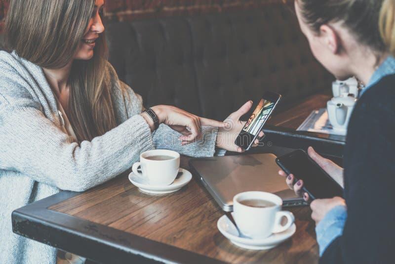 Twee jonge bedrijfs bij lijst zitten en vrouwen die smartphones gebruiken Vrouw die collegabeeld op het smartphonescherm tonen stock foto's