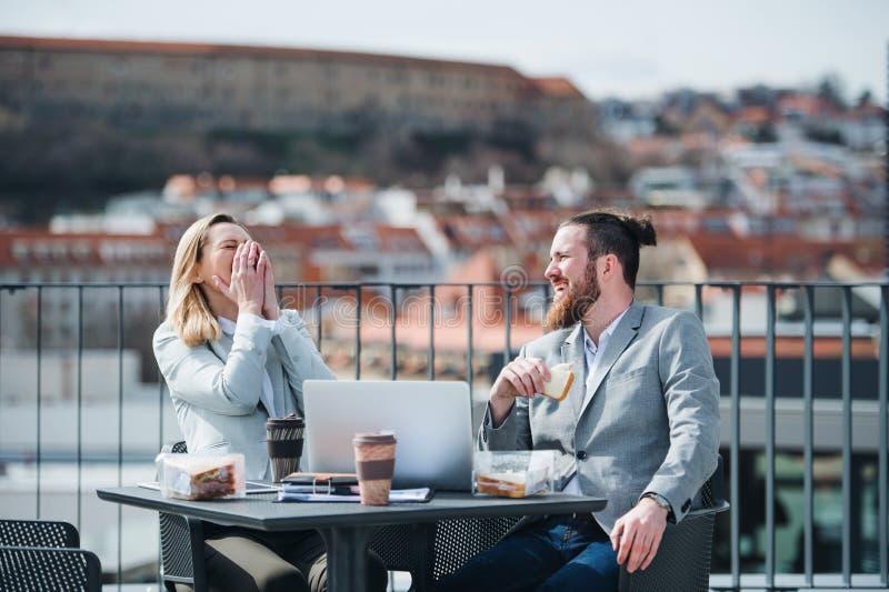 Twee jonge bedrijfsmensen die op een terras buiten bureau zitten, die middagpauze hebben royalty-vrije stock fotografie