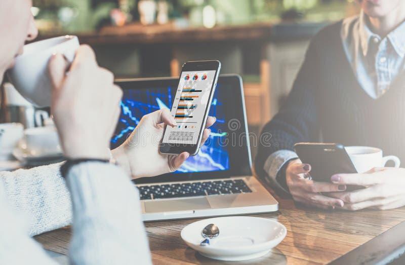 Twee jonge bedrijfsvrouwen die bij lijst in koffie zitten De vrouw kijkt grafieken, diagrammen en grafieken op het smartphonesche stock afbeelding
