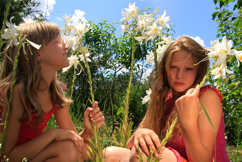 Twee jonge blonde meisjes in de zomertuin stock afbeelding