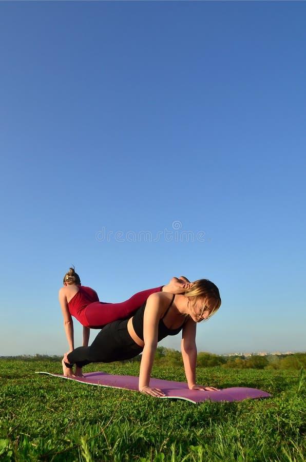 Twee jonge blonde meisjes in sporten past praktijkyoga op een schilderachtige groene heuvel aan royalty-vrije stock foto