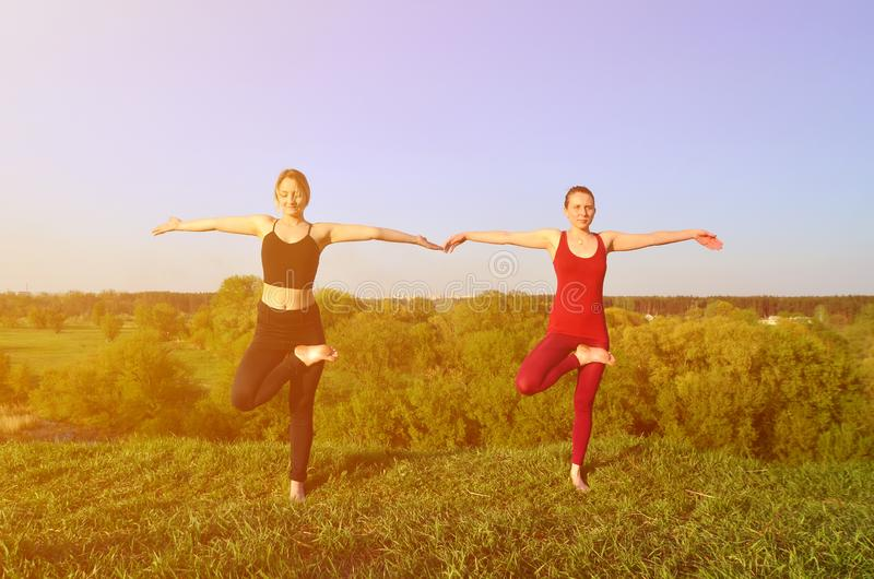 Twee jonge blonde meisjes in sporten past praktijkyoga op een schilderachtige groene heuvel aan royalty-vrije stock foto's