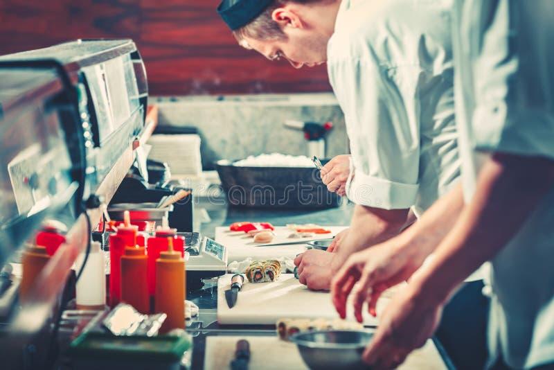 Twee jonge chef-koks in witte eenvormige het voorbereidingen treffen sushi stock afbeeldingen