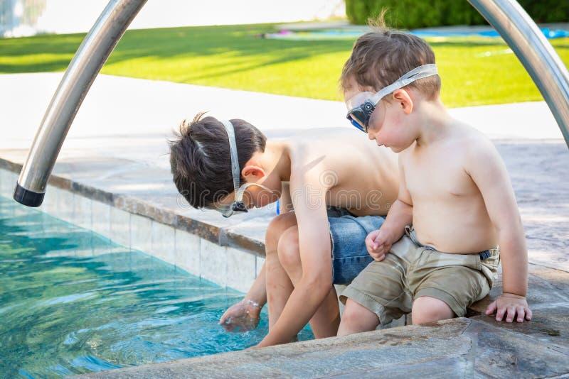 Twee Jonge Chinese Kaukasische Broers door de Pool die Zwemmende Beschermende brillen dragen royalty-vrije stock foto