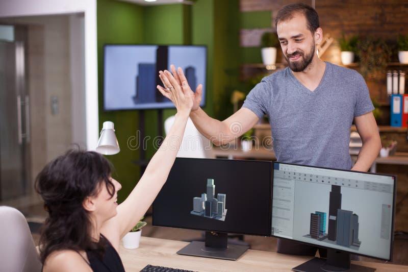 Twee jonge collega's gelukkig over hun project geven een hi5 in hun bureau royalty-vrije stock afbeeldingen