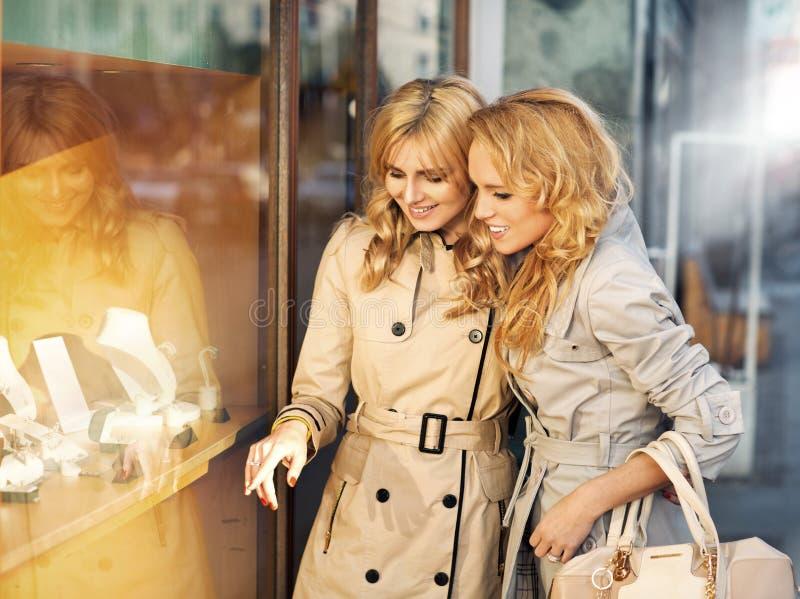 Twee jonge dames die de trouwringen bekijken stock foto