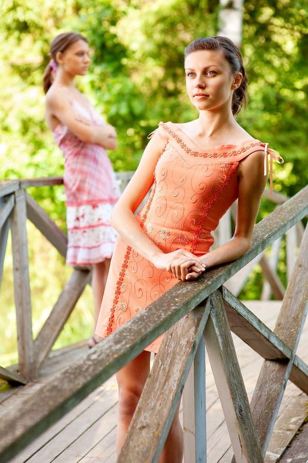 Twee jonge en mooie meisjes bij leuningen royalty-vrije stock afbeelding