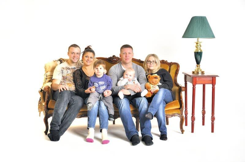 Twee jonge families spelen de dwaas met een kind zitten op een bank royalty-vrije stock foto's
