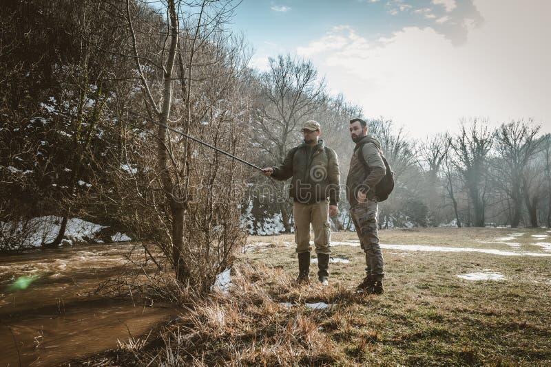 Twee jonge gebaarde mensen die zich naast een gezwelde rivier, het spreken bevinden stock afbeelding