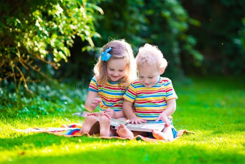 Twee jonge geitjes die in de zomertuin lezen royalty-vrije stock foto