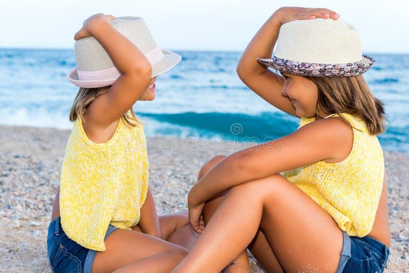Twee jonge geitjes die hoeden op strand dragen royalty-vrije stock foto