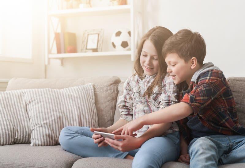 Twee jonge geitjes die op smartphone op bank thuis spelen stock foto's