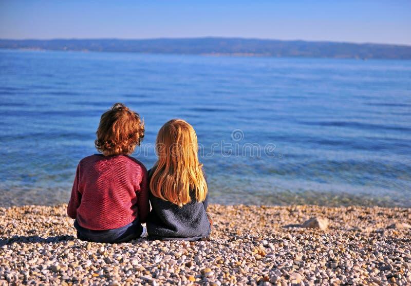 Twee jonge geitjes die op strand zitten en horizon bekijken royalty-vrije stock foto