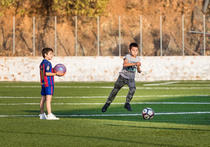 Twee jonge geitjes die voetbal op een voetbalgebied één spelen van hen met het overhemd iin Hydra, Griekenland van Barcelona stock fotografie