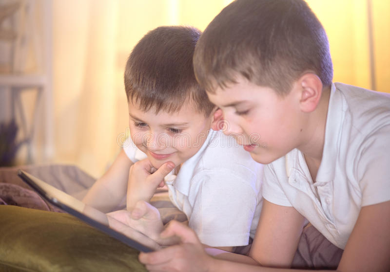 Twee jonge geitjes gebruikend tabletpc in slaapkamer stock foto's