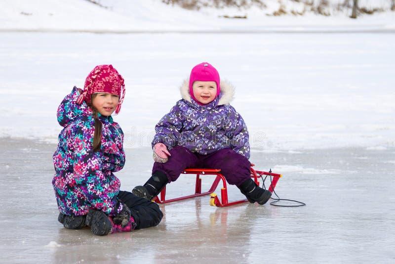 Twee jonge geitjes hebben samen pretzitting op het ijs en het spelen met een sneeuwslee op duidelijke de winterdag stock afbeeldingen