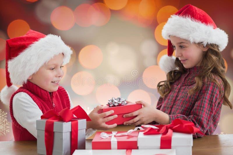 Twee jonge geitjes in santahoed die de dozen van de Kerstmisgift delen royalty-vrije stock fotografie