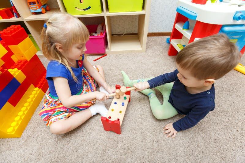 Twee jonge geitjesspel met stuk speelgoed hamers en stokken in kleuterschool stock foto