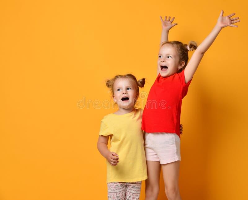 Twee jonge geitjeszusters status die met in rood worden opgeheven en gele handen gillen die omhoog stock afbeeldingen