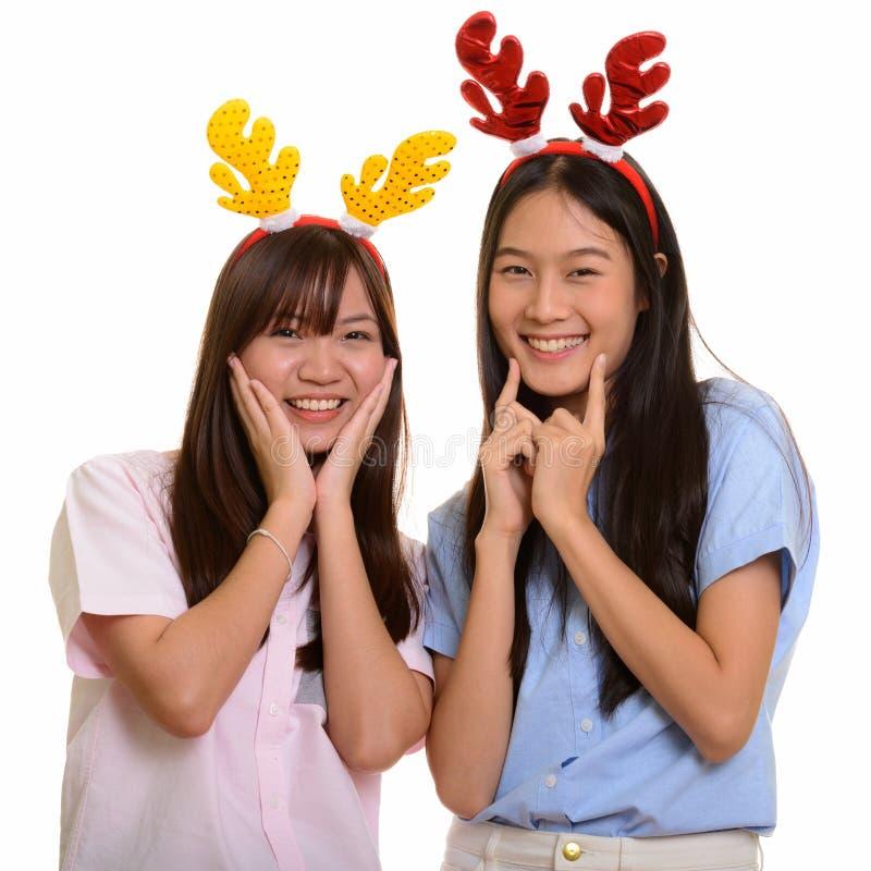 Twee jonge gelukkige Aziatische en tieners die klaar voor glimlachen stellen royalty-vrije stock afbeelding