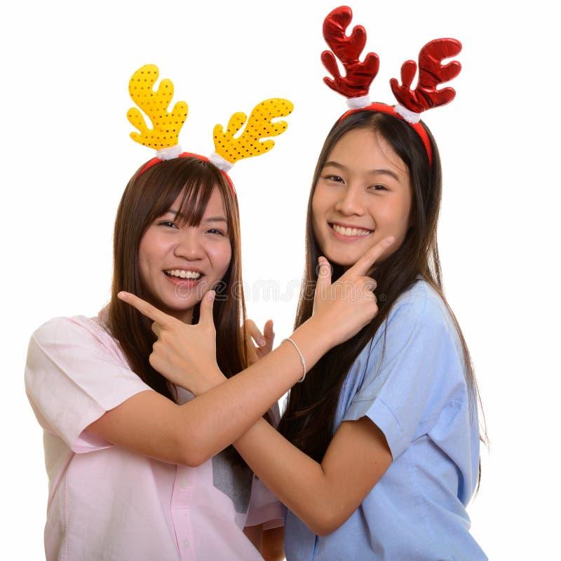 Twee jonge gelukkige Aziatische en tieners die samen glimlachen stellen royalty-vrije stock afbeelding
