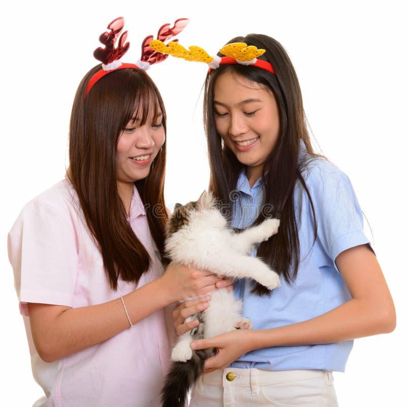 Twee jonge gelukkige Aziatische tieners die en kat gelezen glimlachen houden royalty-vrije stock afbeelding