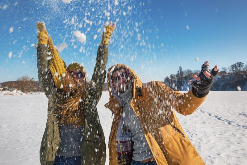Twee jonge gelukkige mensen die sneeuw werpen en pret hebben Selectief F royalty-vrije stock foto's