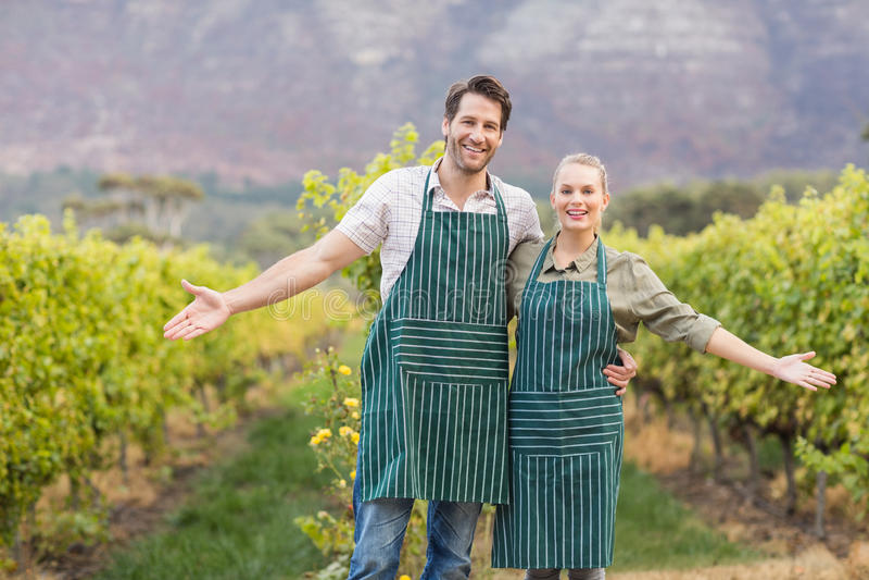 Twee jonge gelukkige wijnhandelaren die hun gebieden tonen royalty-vrije stock afbeelding