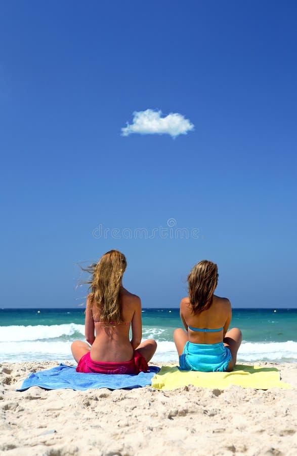 Twee jonge, gezonde sexy vrouwen die op een zonnig strand zitten royalty-vrije stock afbeelding