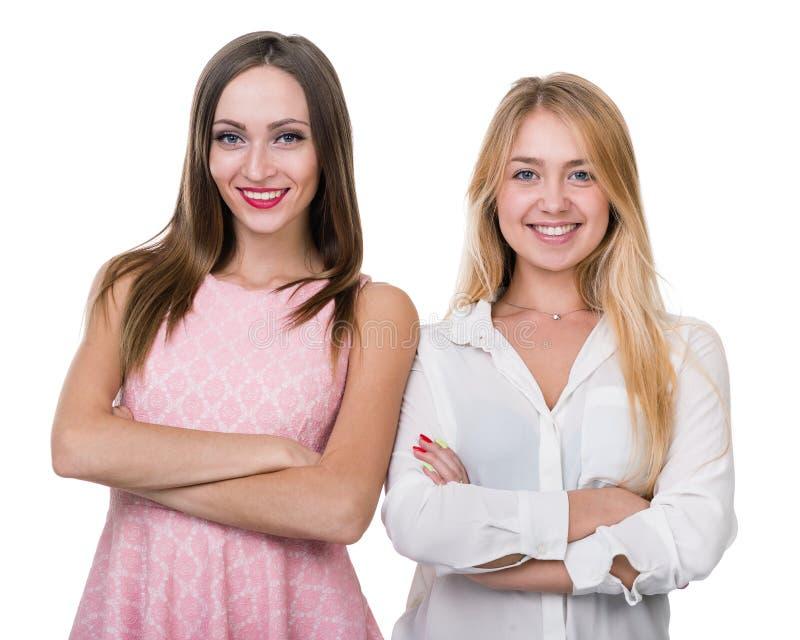 Twee jonge glimlachende die vrouwen, over een wit worden geïsoleerd stock afbeeldingen