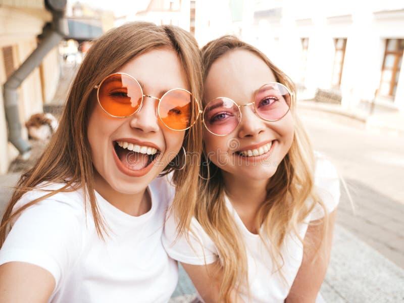 Twee jonge glimlachende hipster blonde vrouwen in kleren van de de zomer de witte t-shirt stock afbeelding