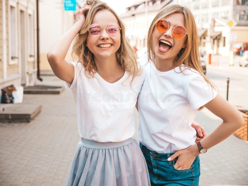 Twee jonge glimlachende hipster blonde vrouwen in kleren van de de zomer de witte t-shirt royalty-vrije stock fotografie