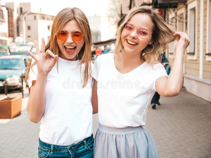 Twee jonge glimlachende hipster blonde vrouwen in kleren van de de zomer de witte t-shirt royalty-vrije stock foto's