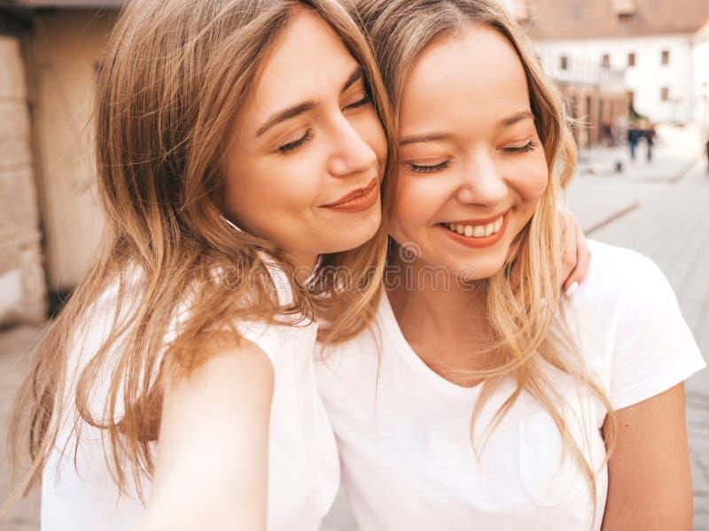 Twee jonge glimlachende hipster blonde vrouwen in kleren van de de zomer de witte t-shirt royalty-vrije stock afbeeldingen