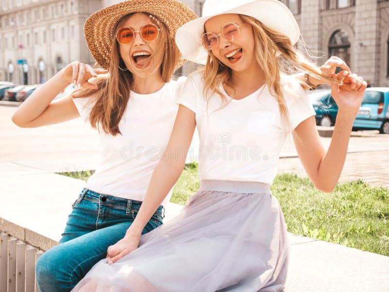 Twee jonge glimlachende hipster blonde vrouwen in kleren van de de zomer de witte t-shirt royalty-vrije stock afbeelding