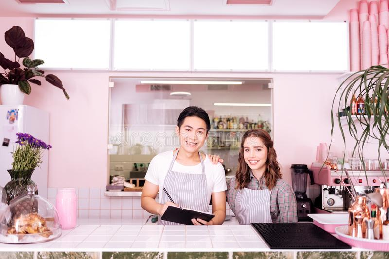 Twee jonge glimlachende kelners die voor werkdag voorbereidingen treffen stock afbeeldingen