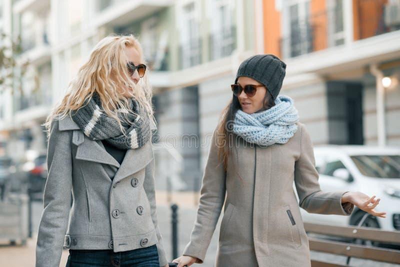 Twee jonge glimlachende mooie vrouwen die in warme kleren onderaan de stadsstraat lopen met een en reiskoffer, vrouwen die lachen stock afbeelding