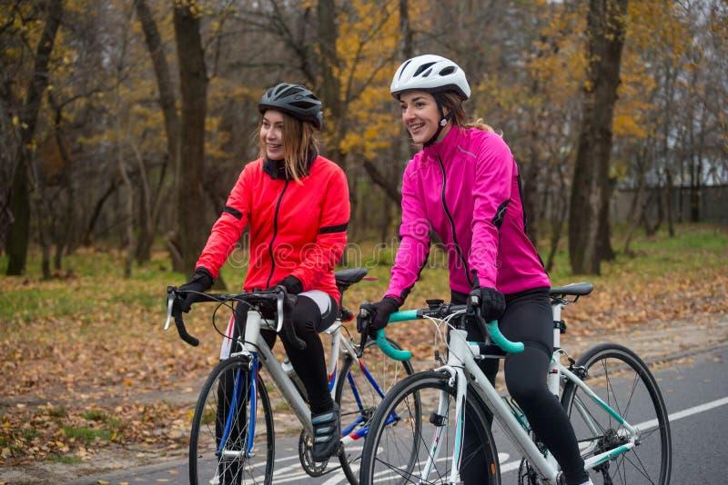 Twee Jonge Glimlachende Vrouwelijke Fietsers met Wegfietsen die en in Park in Koud Autumn Day rusten Gezonde Levensstijl royalty-vrije stock foto's