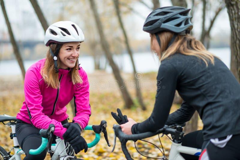 Twee Jonge Glimlachende Vrouwelijke Fietsers met Wegfietsen die en in Park in Koud Autumn Day rusten Gezonde Levensstijl stock afbeelding