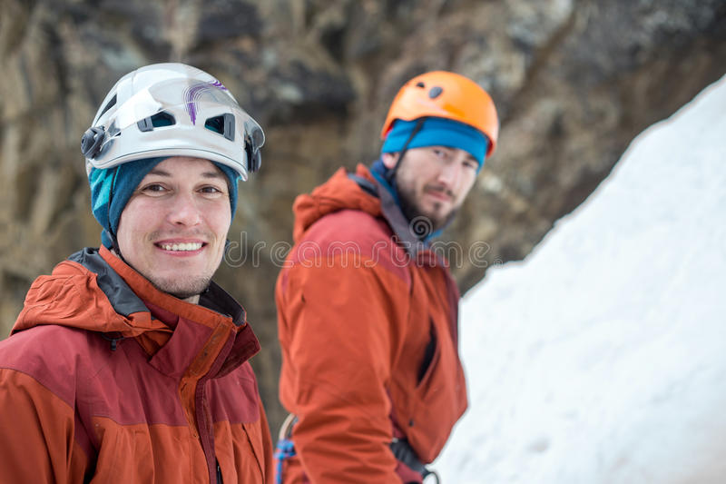 Twee jonge ijsklimmers die in sporthelmen ons op ijsachtergrond bekijken royalty-vrije stock afbeeldingen
