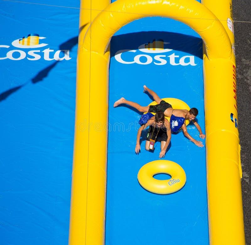 Twee jonge jongens die in de langste die waterdia spelen gingen in het Guinness Book van Verslagen binnen voor Costa Cruises Fest stock afbeeldingen