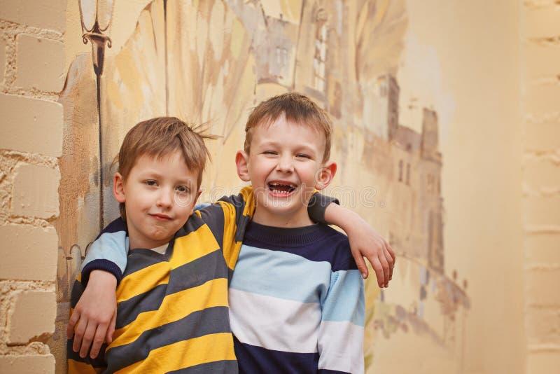 Twee jonge jongens in openlucht het glimlachen en lach Conceptenvriendschap stock foto's