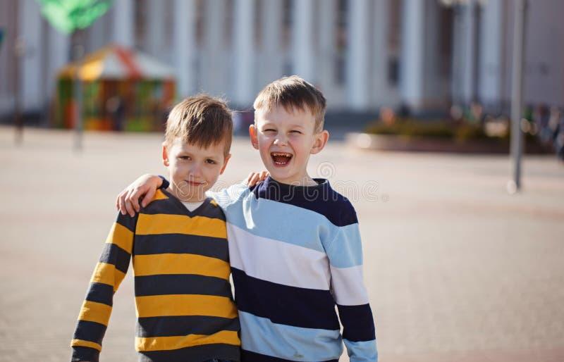 Twee jonge jongens in openlucht het glimlachen en lach Conceptenvriendschap stock afbeeldingen