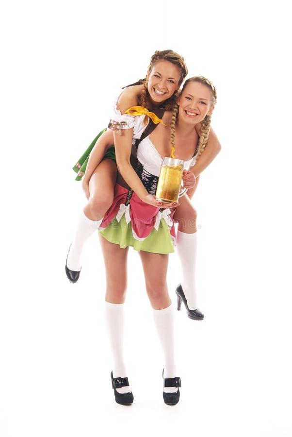 Twee jonge Kaukasische Beierse vrouwen met bier stock foto