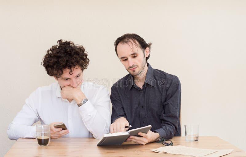 Twee jonge Kaukasische collega's die bij de lijst in het bureau met lichte achtergrond zitten royalty-vrije stock afbeeldingen