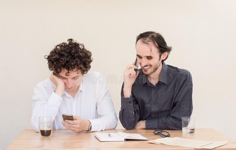 Twee jonge Kaukasische collega's die bij de lijst in het bureau met mobiele in hand telefoons zitten royalty-vrije stock afbeeldingen