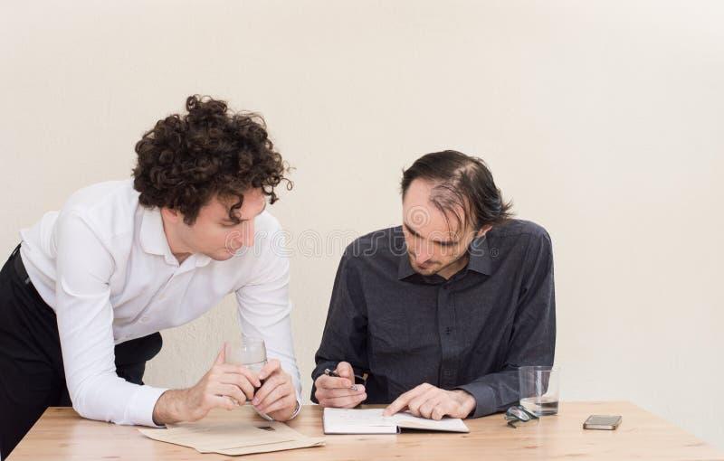 Twee jonge Kaukasische collega's die in het bureau met lichte achtergrond bespreken stock fotografie