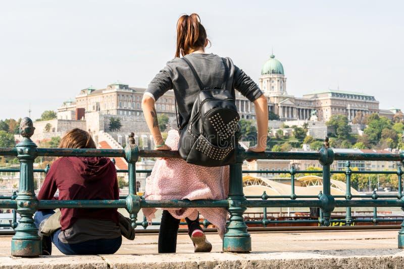 Twee jonge Kaukasische vrouwen die en tegen een staaltraliewerk door de rivier van Donau in Boedapest Hongarije zitten leunen stock foto's