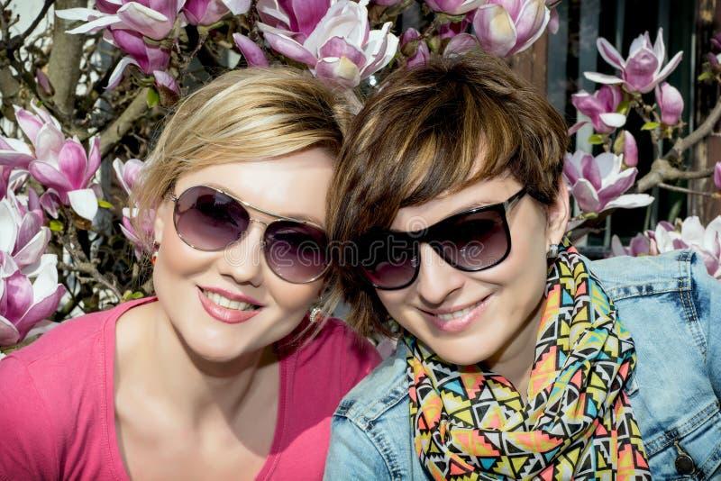 Twee jonge Kaukasische vrouwen die met bloeiende magnolia stellen stock afbeelding